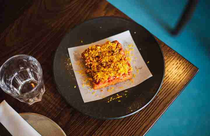 Plated dish of a square of fried potato hash topped with raw beef tartare and grated yellow cured egg yolk on edge of table with vivid blue floor below