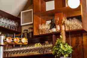 Amok - detail of bar showing piano key edging, polished glasses lined up on shelves and bottles