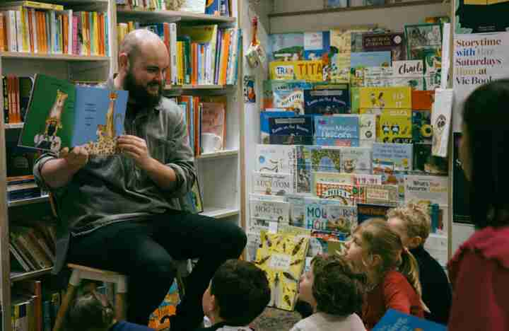 Man reading book to children at Vic Books