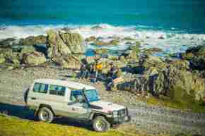 Seal Coast Safari tours ocean scenery red rocks bays 4WD truck dirt gravel road sea tourists family kids children waves